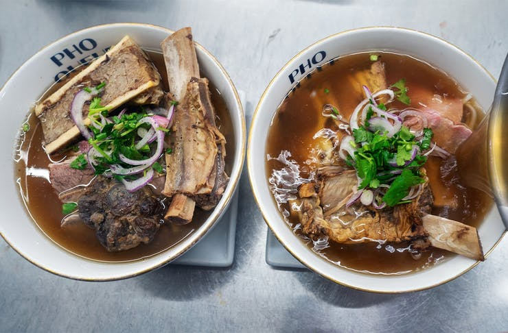 two bowls of pho side by side