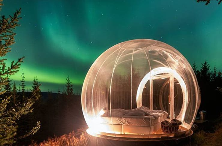 A clear bubble with a bed inside underneath the Northern Lights.