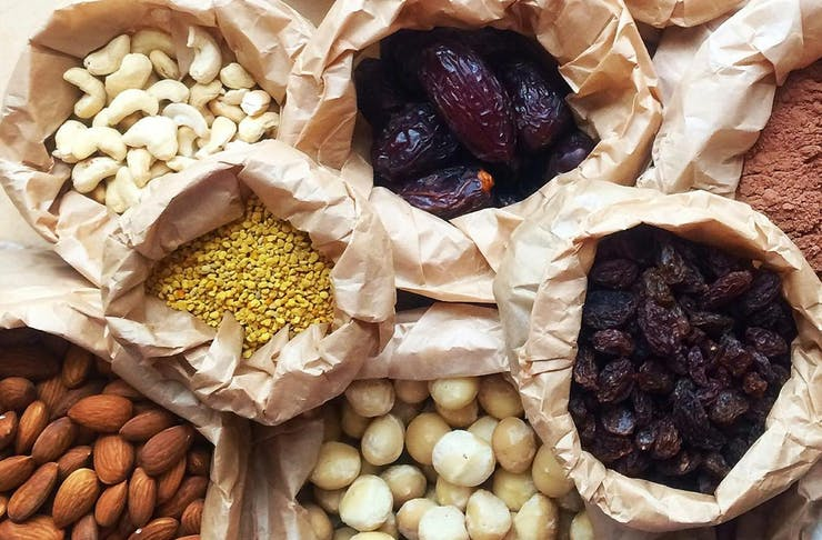 A collection of brown paper bags, filled with bulk foods like nuts, seeds and dried fruits.
