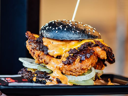 A burger stacked with chicken and beef inside a charcoal bun. Cheese is dripping.