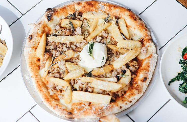 a pizza topped with chips and burrata