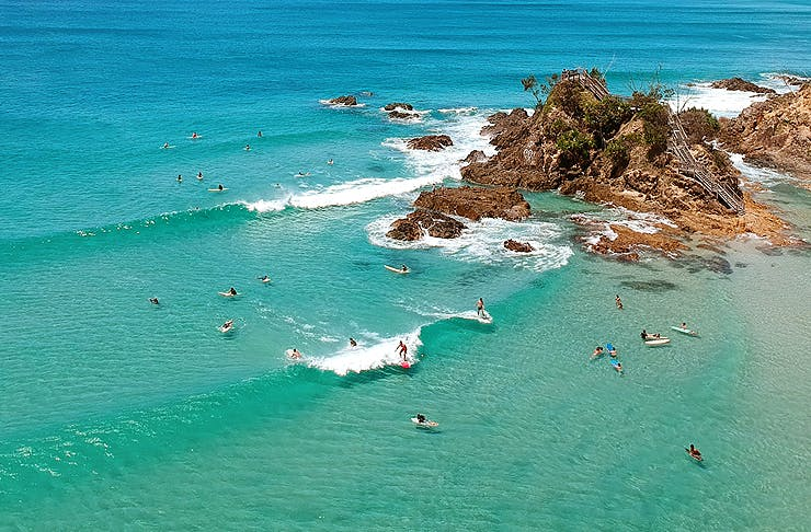 Bird's eye view over a turquoise waves and sandy beach.