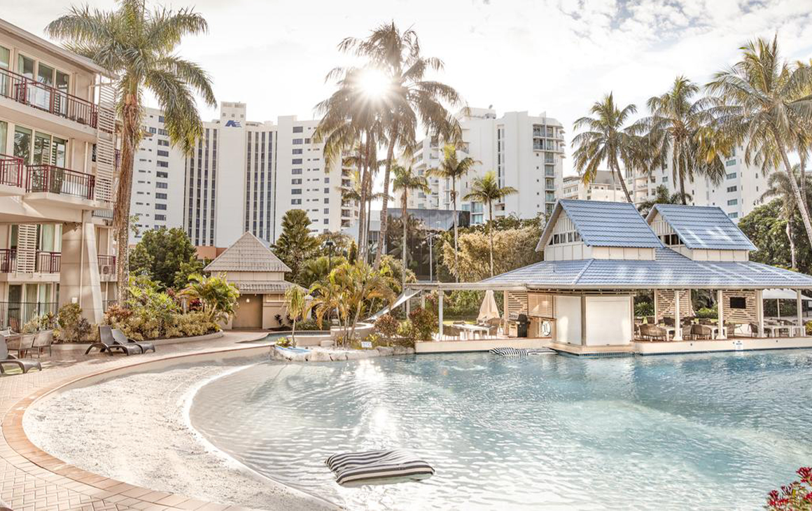 a hotel pool with a sandy beach