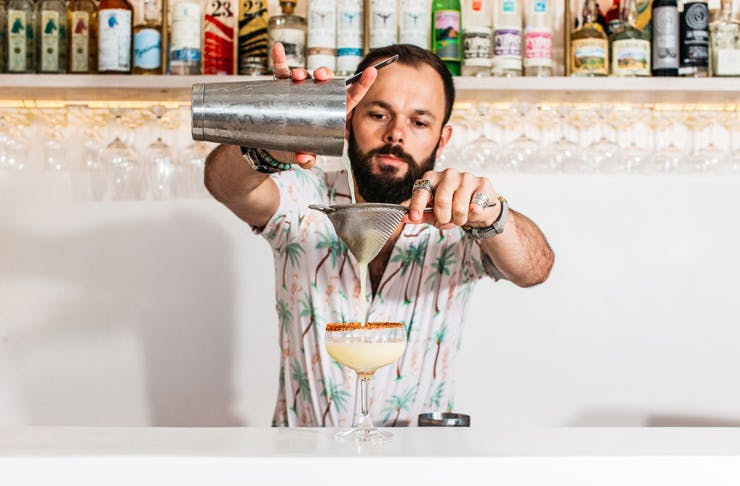 A bartender pours a drink at Calita.