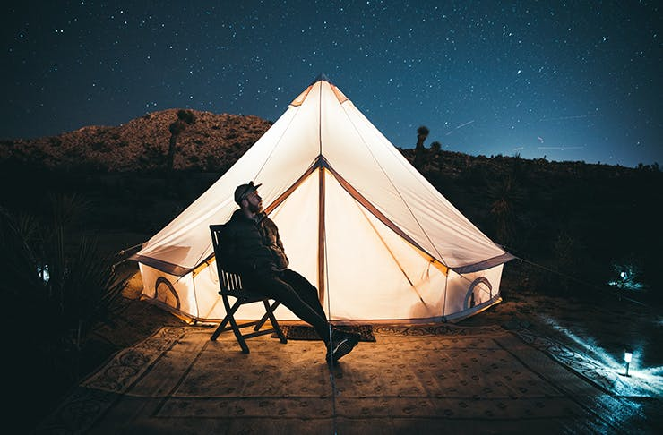 A man sits on a camping chair outside of his tent, underneath a starry sky.