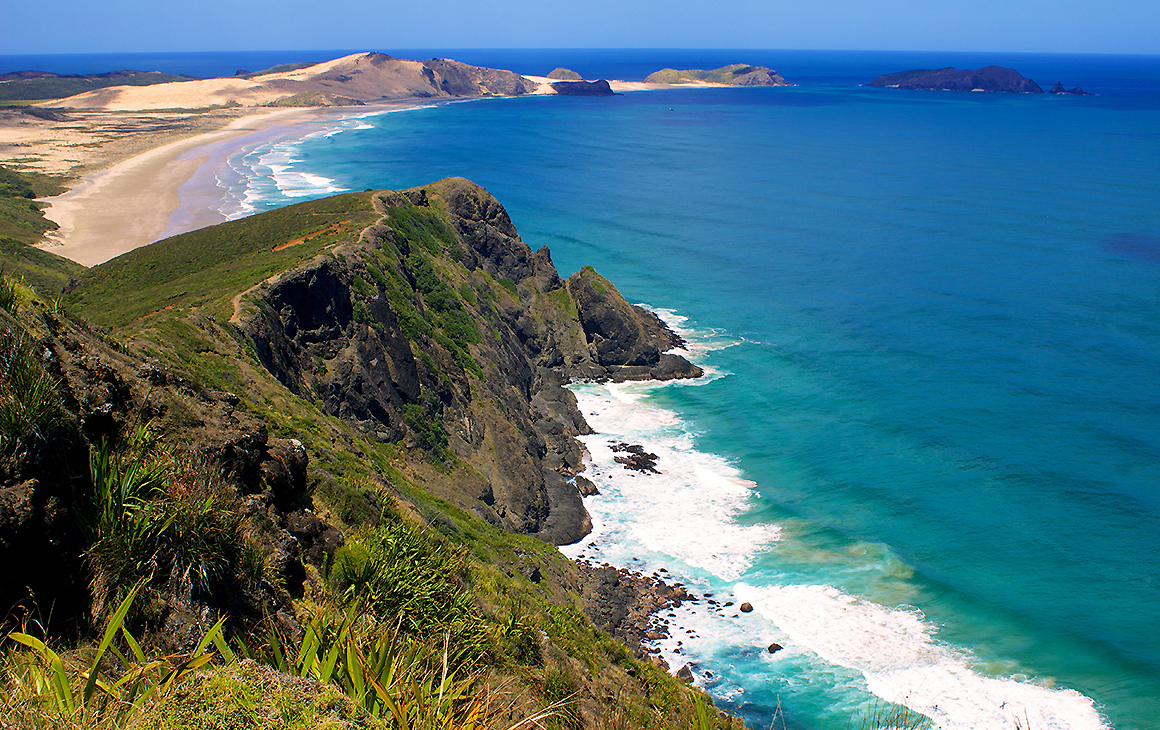 A view of beautiful cape Reinga in the far north showing a long white sand beach with the water lapping on the shore.