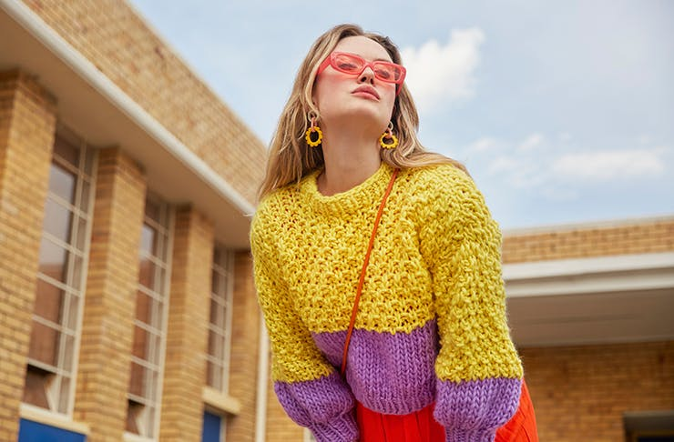 A woman in a colourful knitted sweater looking up at the sky.
