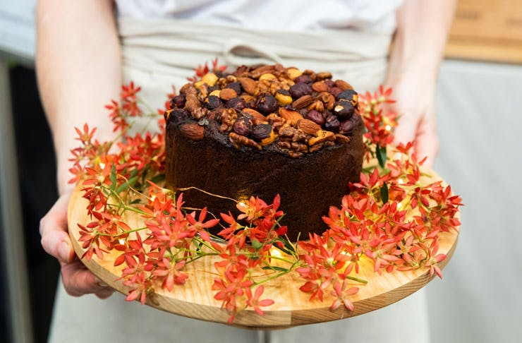 A person holding a Christmas cake decorated with flowers.