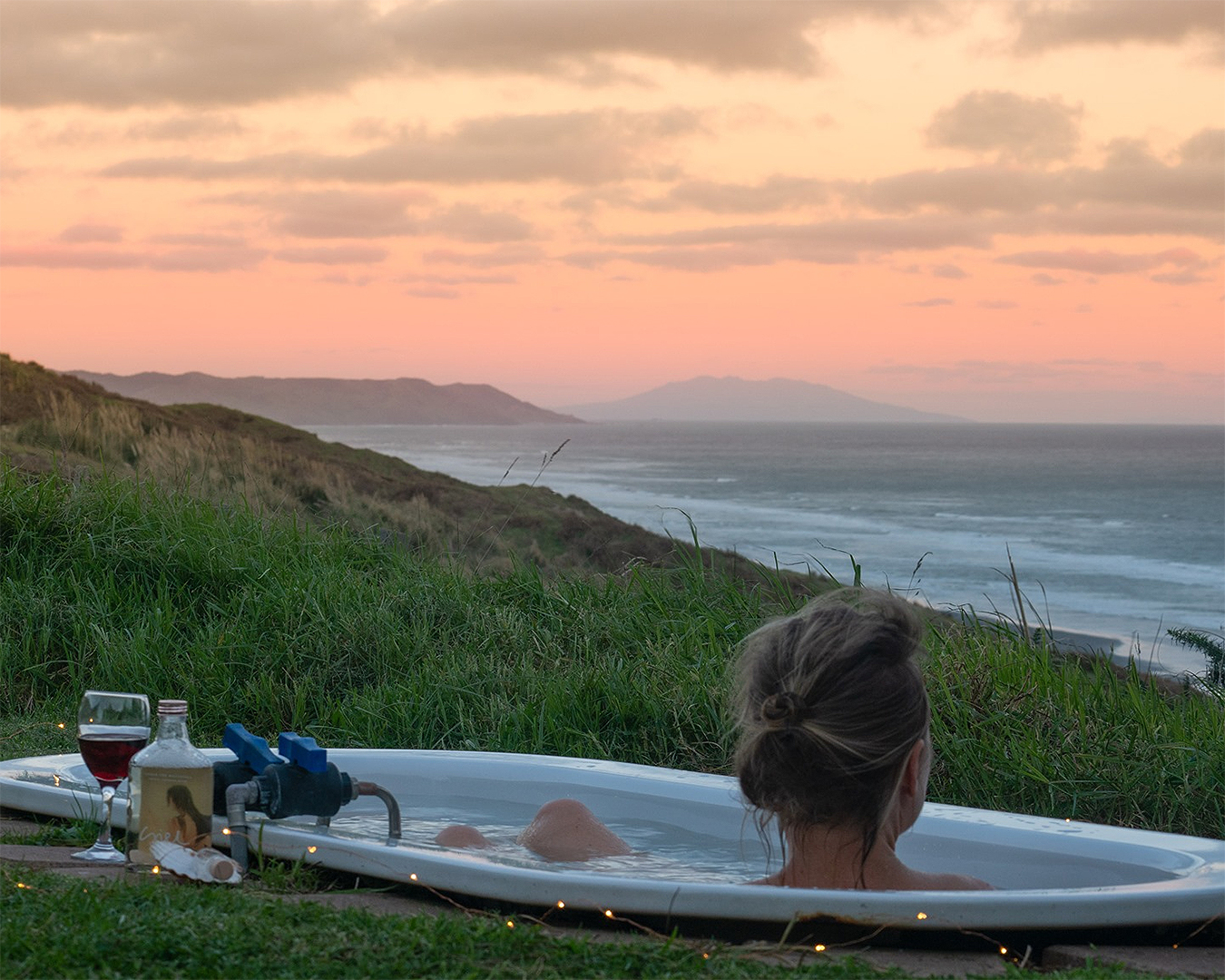 A girl looks over the sea while sitting in an outdoor bath with a glass of wine nearby. One of the best glamping experiences to be had near Auckland.