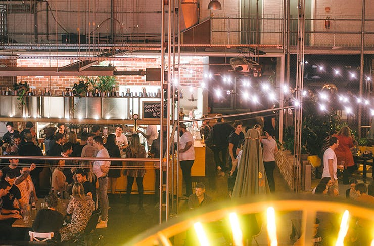 People drinking at a brewery underneath fairy lights.
