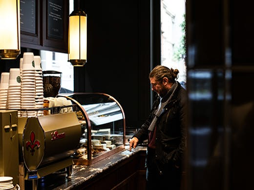 A man standing next to a coffee machine in a moody cafe.