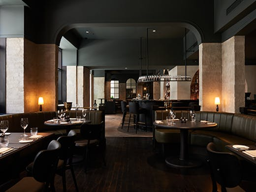 A moody fine diner with wood finishings and warm lighting.