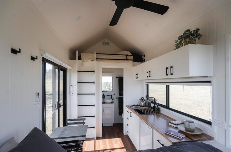 the inside of a tiny house, with a loft bed and kitchen