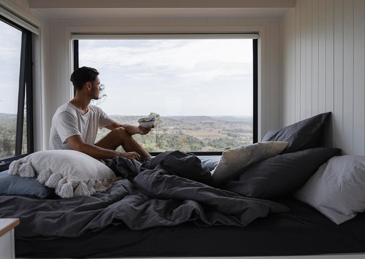 a person in a bed with windows overlooking a scenic view
