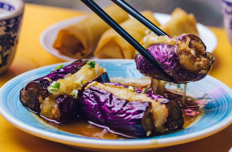 Delicious looking food is being picked up by chopsticks