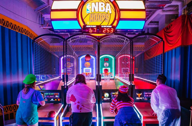 four people playing a basketball arcade game