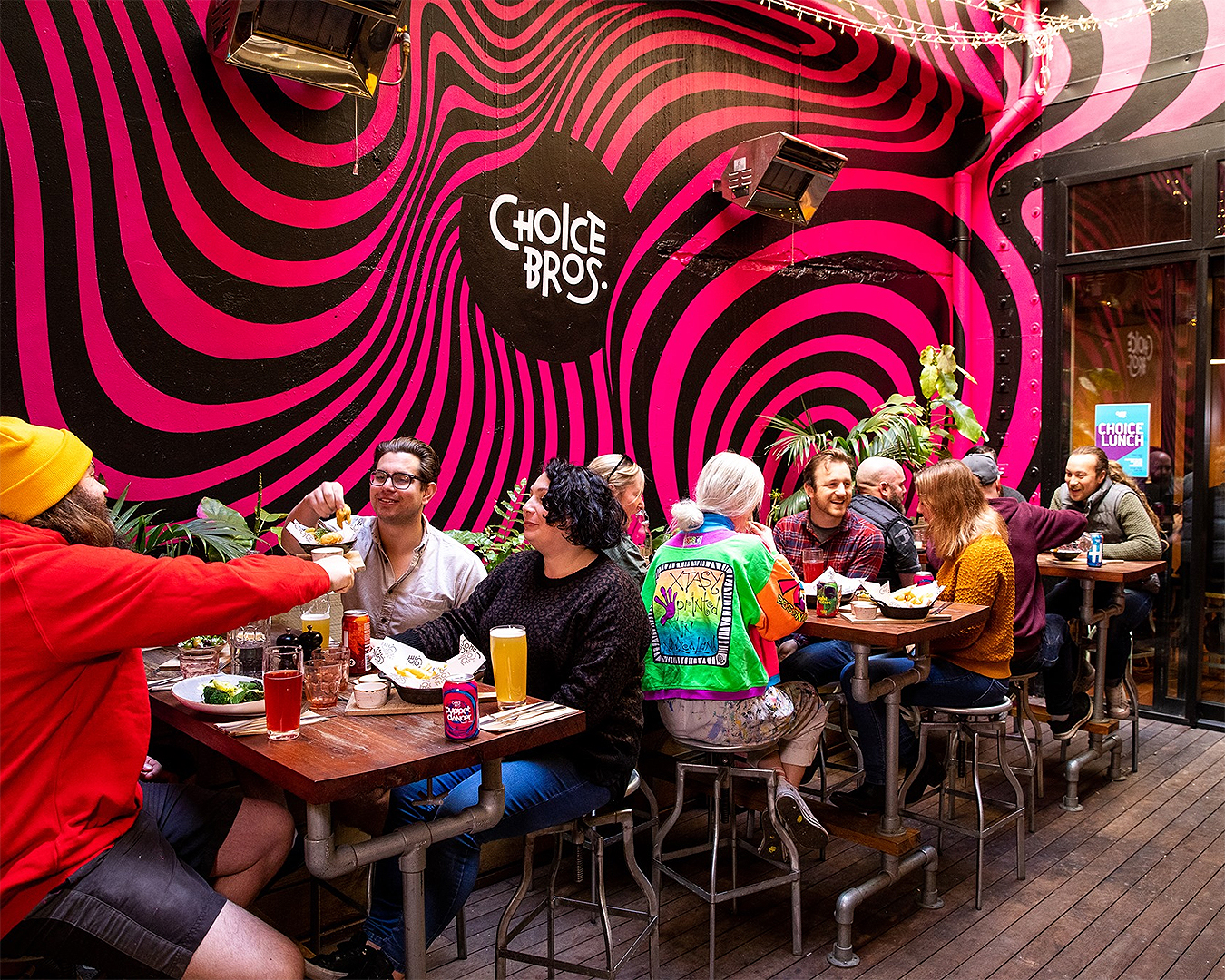 People revelling at Choice Bros at tables eating and drinking with a cool psychedelic mural on the wall.