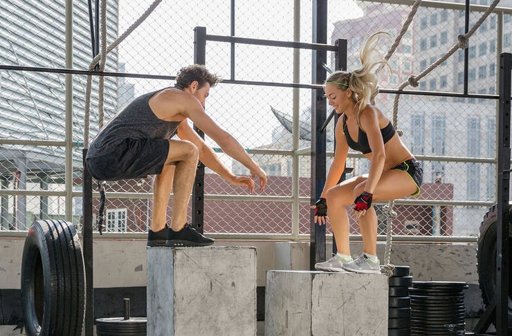 Two people jump on concrete blocks while working out.