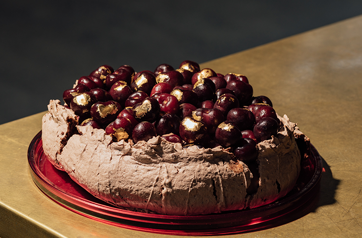 A chocolate pavlova on a table covered in cherries.