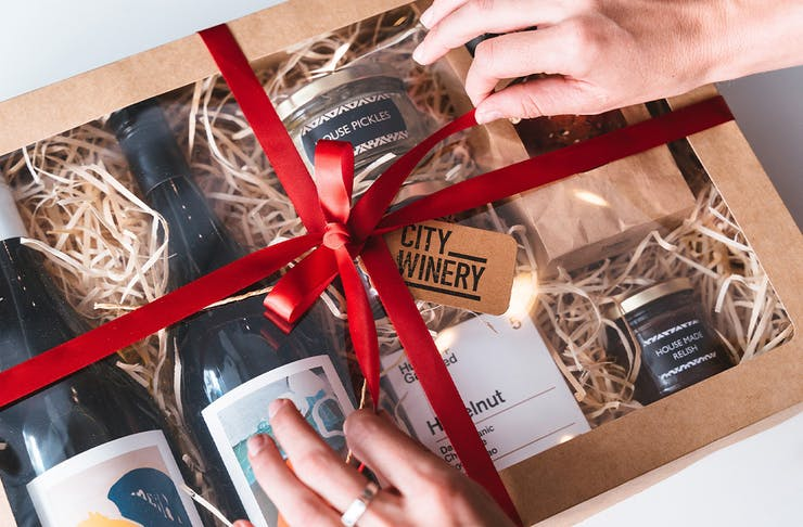A person tying a ribbon on a Christmas Hamper box