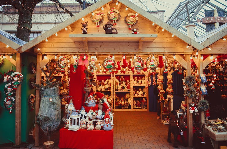 a christmas market stall filled with christmas toys and ornaments