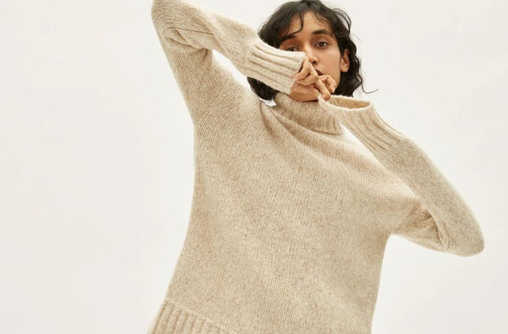 A model wearing a white Everlane sweater.