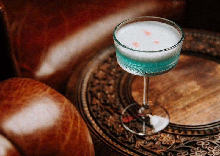 a blue cocktail on a table