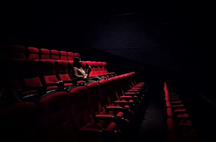 Woman sitting in dark cinema eating a choc top.