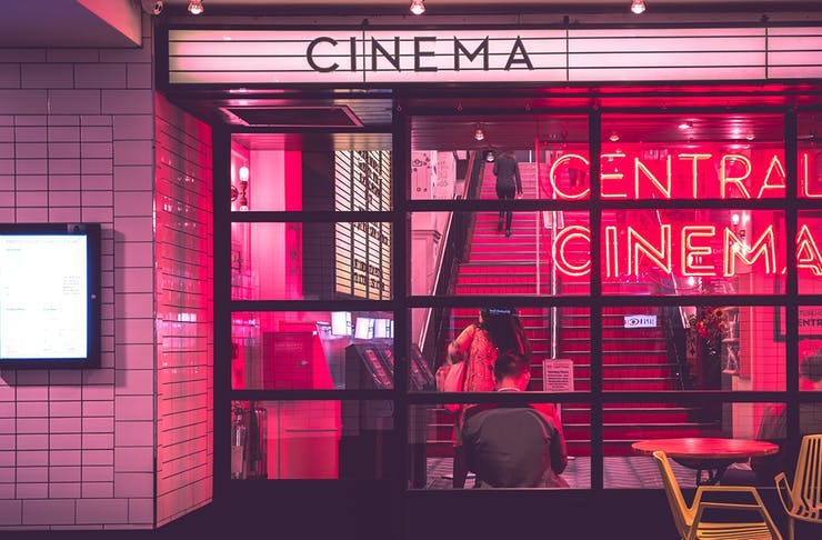 A pink, neon-lit cinema shines through a glass facade. The sign above the entrance reads 'Cinema'.
