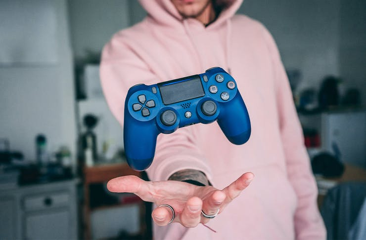 a man in a pink hoodie holds out a gaming control