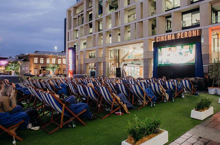 Movie goes sit in blue and white chairs as they watch a film on an outdoor screen in the day light
