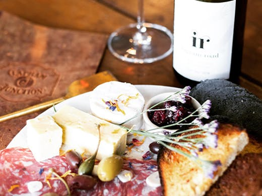 A platter of charcuterie next to a bottle of wine