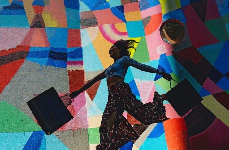 A girl swinging some shopping bags in front of a painted wall.