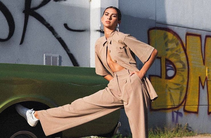 A girl wearing a tan suit leans her foot on a cool retro truck. She's wearing white Veja sneakers.