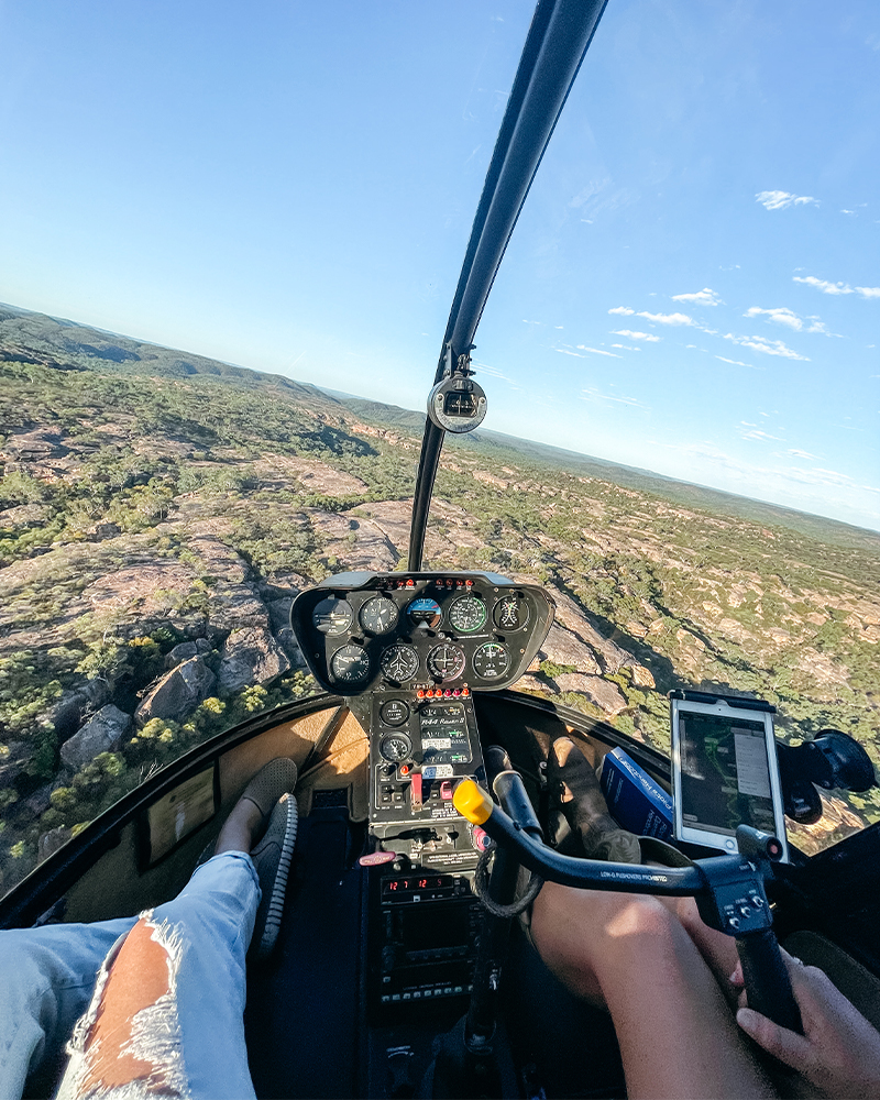 view through the front window of a helicopter, looking at the scenery below