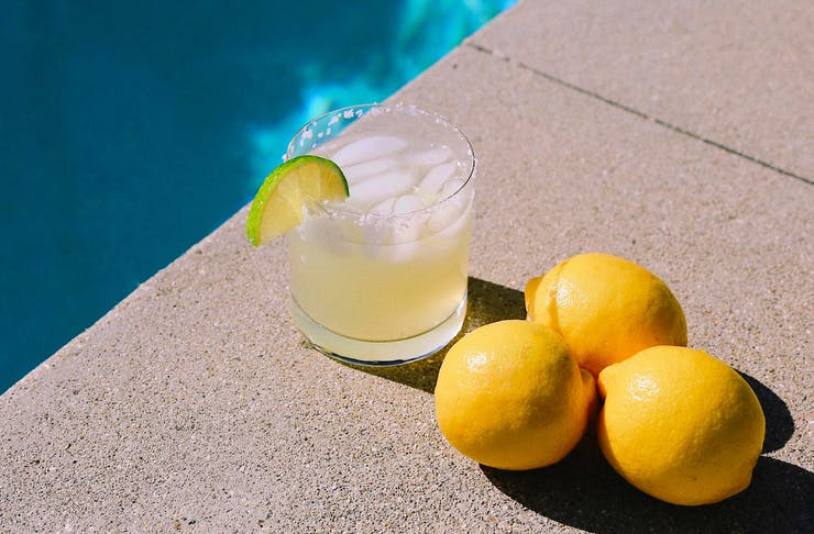 A cocktail rests poolside next to three lemons.