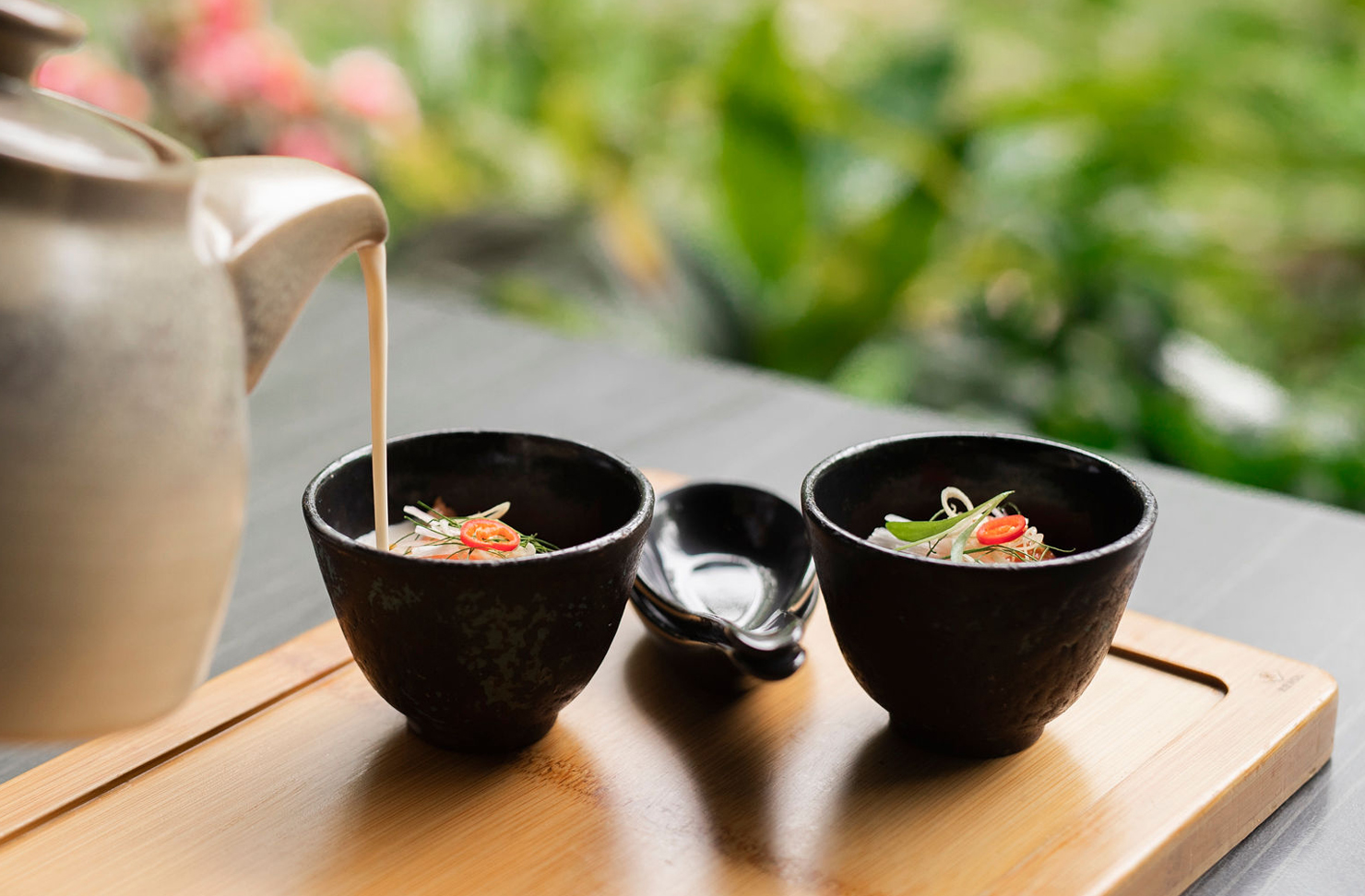 A top lay image of a teapot pouring coconut salmon soup into two small black bowls.