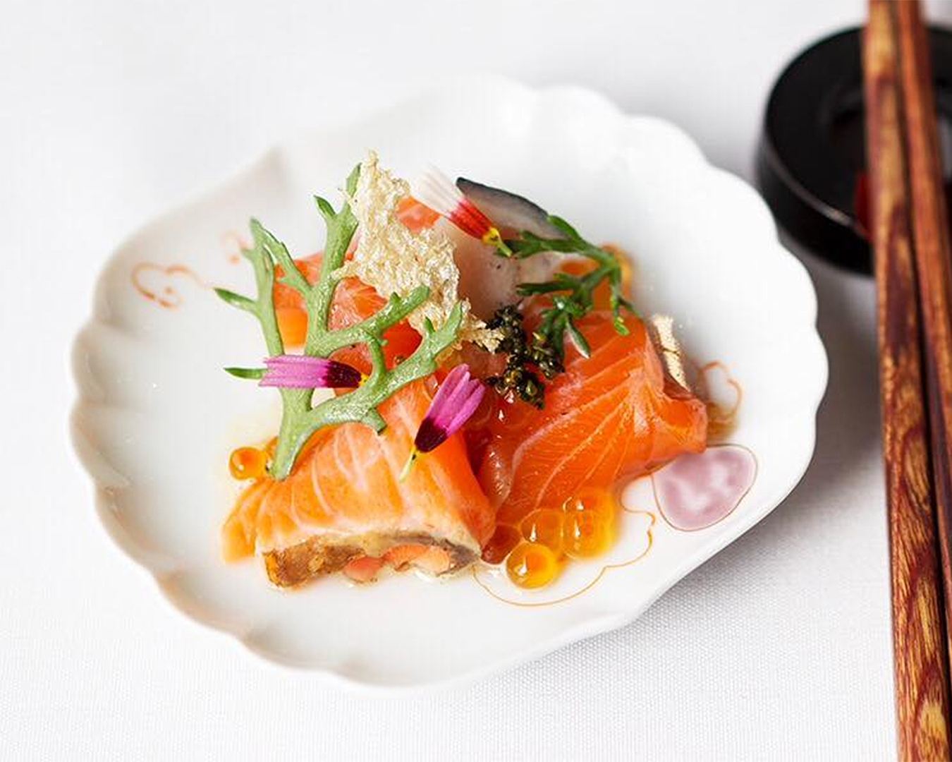 A sashimi dish sits on a white plate with chopsticks at the ready.