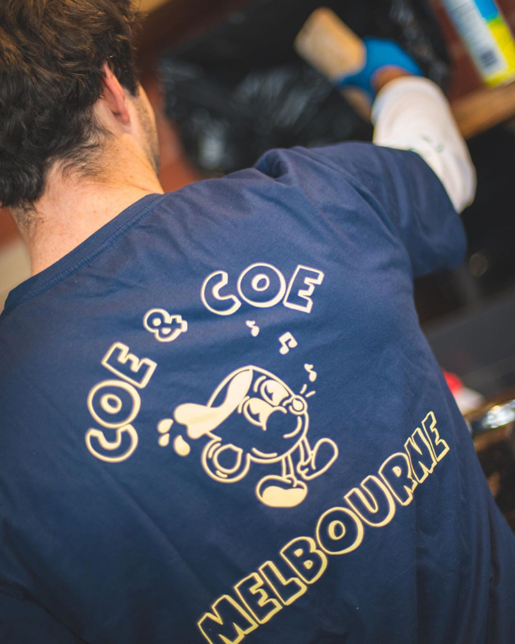 A man wearing a navy toshirt with the words Coe & Coe printed on the back.
