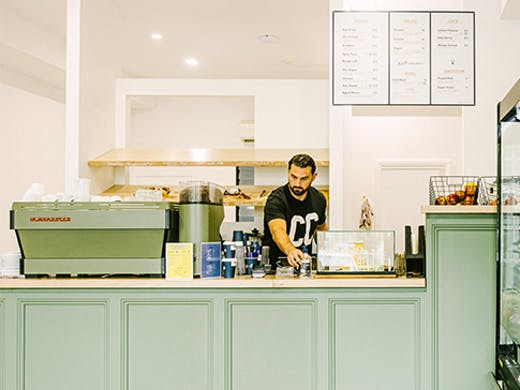 a man behind a mint green counter in a cafe