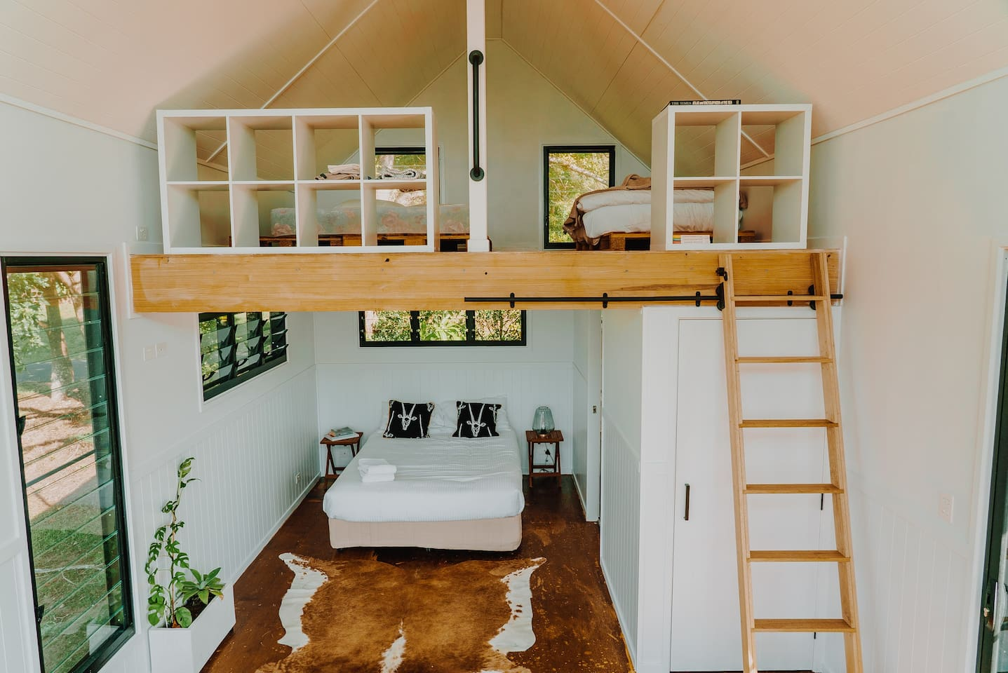 looking into a bedroom with a loft area over the bed