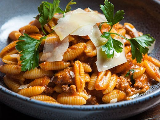 a bowl of shell pasta with bolognaise sauce