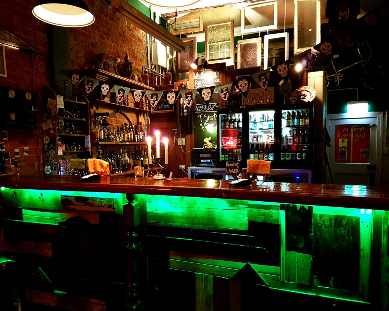 A dimly lit bar with neon lighting under the bar counters
