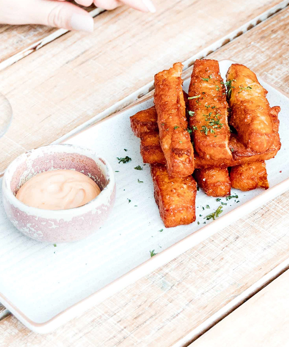 a plate of haloumi chips and dipping sauce