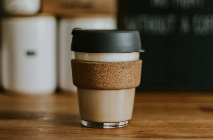 A glass keepcup with a black lid, filled with milky coffee