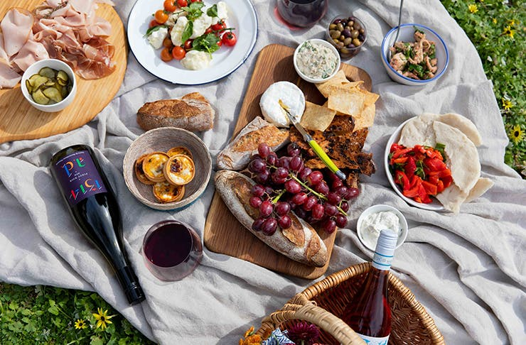 a picnic spread in the grass including several bottles of wine.