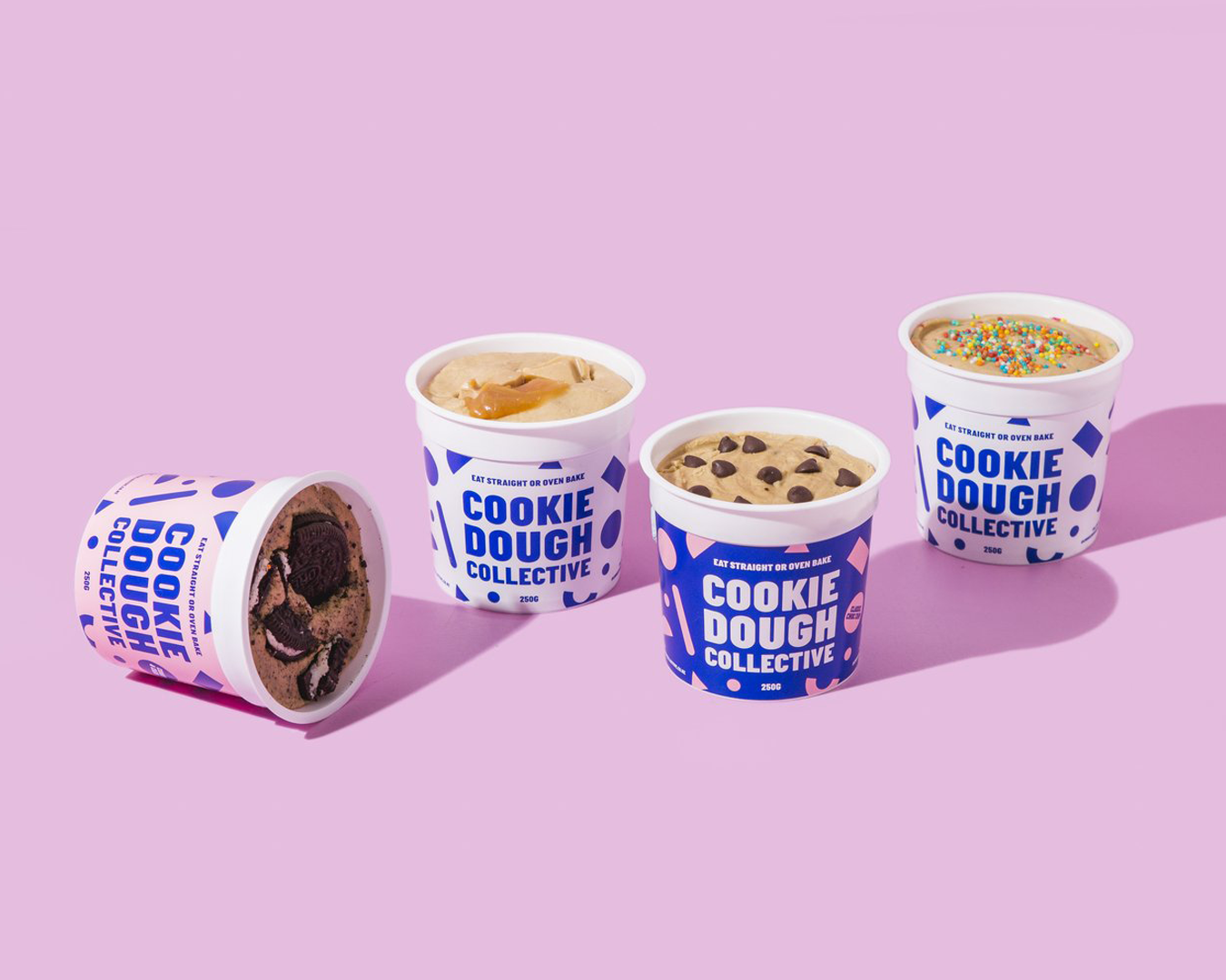 Four plastic tubs of cookie dough in different flavours on a pink background