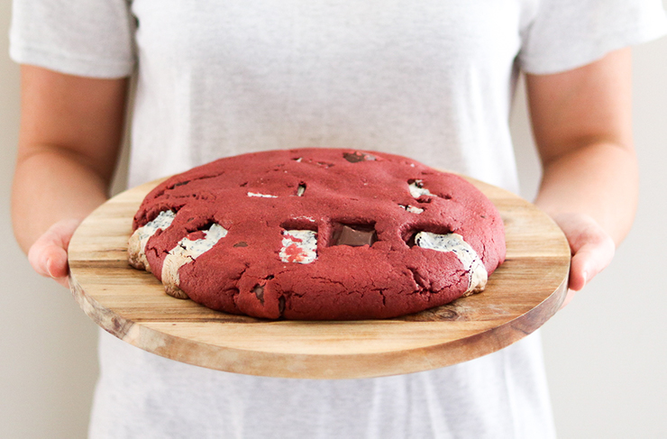A person in a white shirt holding a wooden board atop which sits a large red velvet pizza cookie.