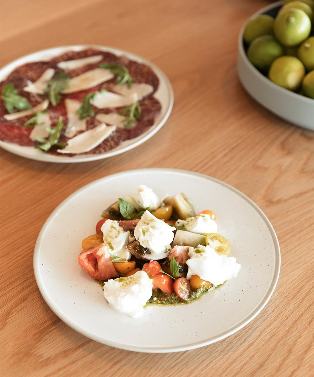 a plate of mazzarella salad and breasola