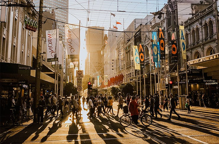 a crowd of people walking in melbourne at golden hour